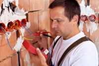 Electrician using a voltage meter on wiring in a house