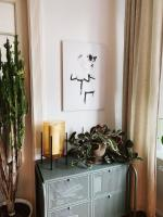 Dining room buffet table with a candle, plant, and painting