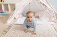 Baby crawling with teepee in the background