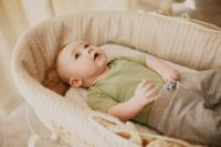 Baby in bassinet with green tshirt and gray pants