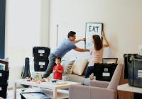 Couple and child putting up a framed picture