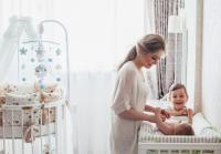 Mom changing baby in nursery with white crib and mobile