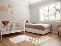 Nursery with clouds on wall crib and plush toy