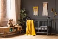 Plush toy and dark crib with yellow blanket and plant