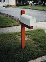 Red and white mailbox in front of house lawn