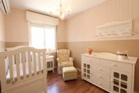 Soft pink nursery with all white furniture