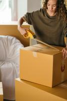 Woman packing and closing cardboard boxes