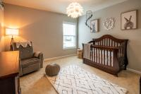 Wooden crib with gray chair