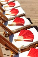 Red folding paper fans on white seats at wedding