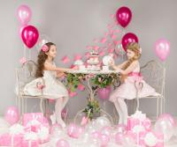 Two girls playing at pink themed party