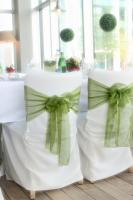 White chairs with green ribbons at wedding reception